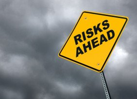Risks ahead road sign in front of cloudy sky background